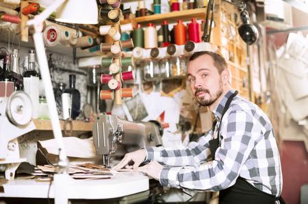 Adult man worker qualitatively stitching belt in leather workshop