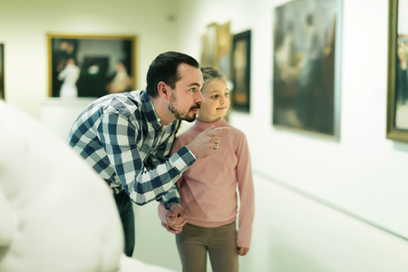 Ordinary father and daughter exploring religious art in museum
