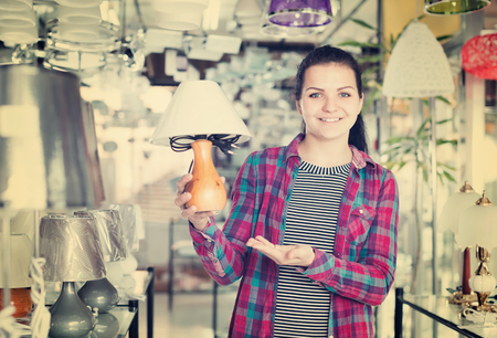 Young glad girl in lighter shop choosing stylish and modern lamp for house interior Imagens