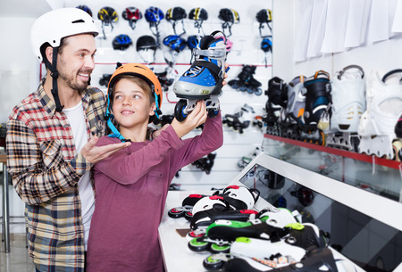 Smiling father and his son examining various roller-skates in sports store. Focus on both persons