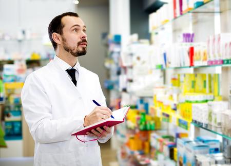Handsome male pharmacist checking assortment of drugs in pharmacy Stock Photo