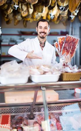 happy russian male shop assistant demonstrating sliced bacon in butcher's shop Reklamní fotografie