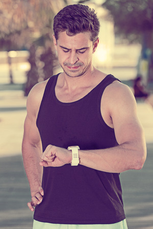 Portrait of athletic man in sportswear seriously looking at watch