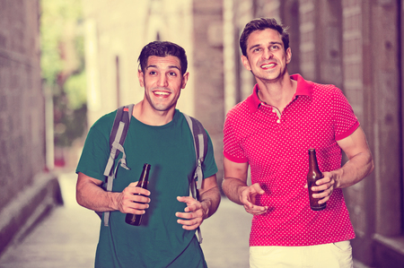 Happy smiling men friends are drinking beer in time walking in city.