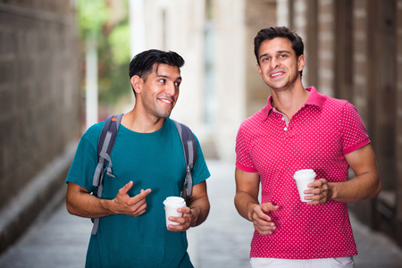 Happy positive smiling men friends are drinking coffee in time walking in city.