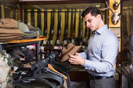Handsome adult male choosing hunt equipment in store