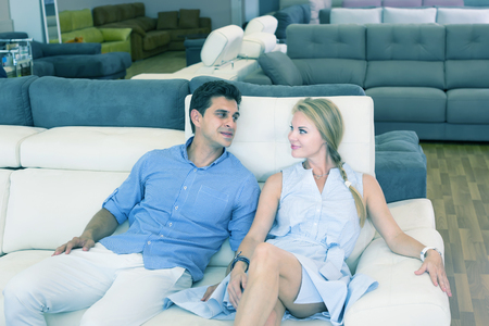Man and woman are selecting of new sofa in furniture store.