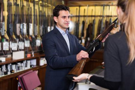Confident salesman in gun shop showing rifle to female client