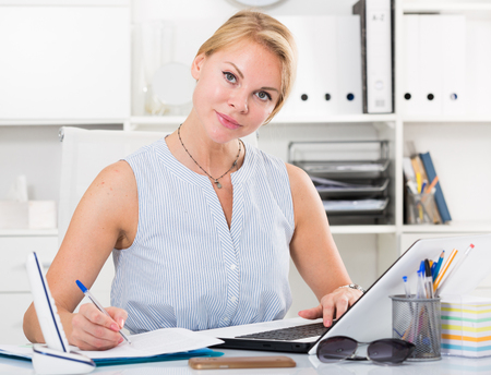 portrait of young russian  business woman  writing and working with laptop in office