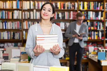 Thoughtful girl student standing in bookshop on background with colorful bookshelves
