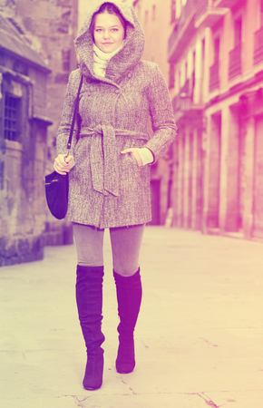 positive girl teenager in the historical city in hood outdoors