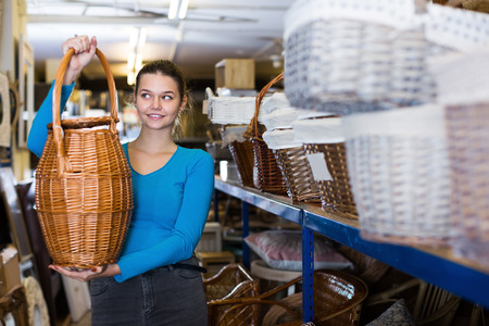 Portrait of young woman consumer holding wicker barrel in decor items store