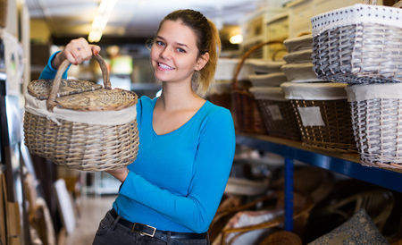 teenager demonstrates the choice of the picnic basket in shop for decor