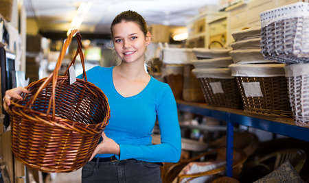 Glad female standing with wicker basket in decoration and furniture store