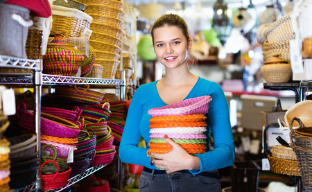Cheerful  smiling female teenager and assortment of wicker basket in decor store