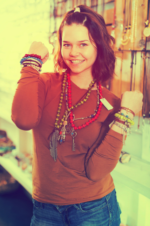 Cheerful young woman selling different pendants and bracelets in the market Banque d'images
