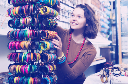 Young girl seller offering colored bracelets on the stand