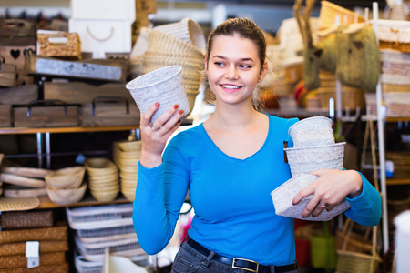 Happy cheerful female teenager and assortment of wicker basket in decor store