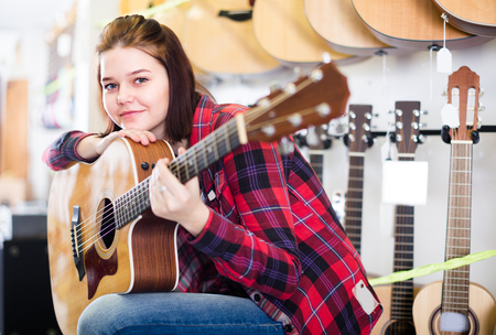 Young female is deciding on acoustic guitar in guitar shop.
