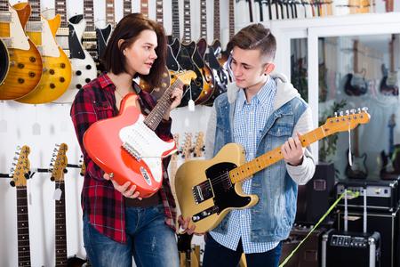 Girl and boy are deciding on suitable amp in guitar shop.