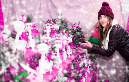 Pretty young woman choosing Christmas decoration at market in evening time Standard-Bild