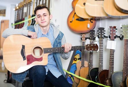 Nice teenage customer deciding on acoustic guitar in guitar shop Foto de archivo