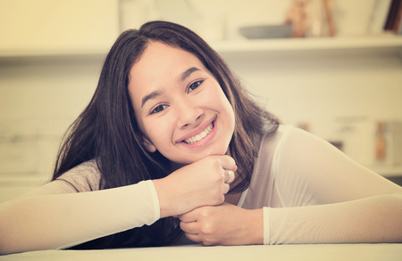 Positive teenager girl smiling at home sitting at the table