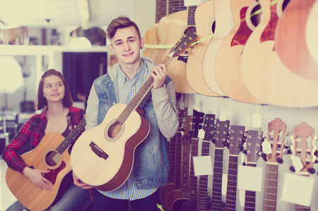 english teenage customers deciding on suitable acoustic guitar in guitar shop