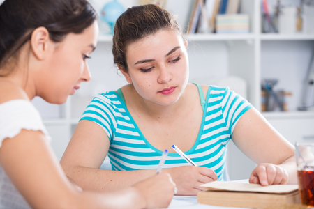 Teenagers girls studying with textbook at table at home and helping each other