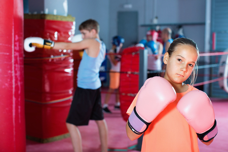 Young  serious girl in gloves posing during boxing training at gym