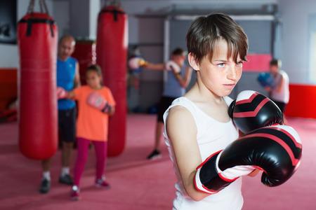 Teenage boxer in gloves posing during boxing training at gym