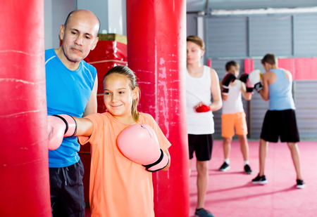 Positive little girl with boxing gloves posing in defended stance Stock Photo