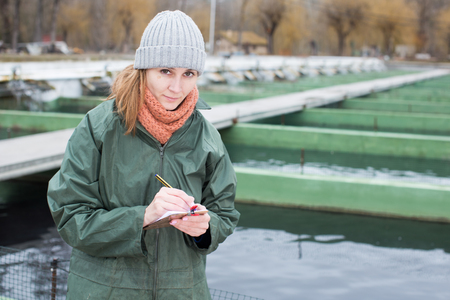 Young female worker of fish farm standing near fish tanks writing something in notebook