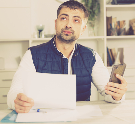 Portrait of male business working in office with documents, holding mobile Stock Photo