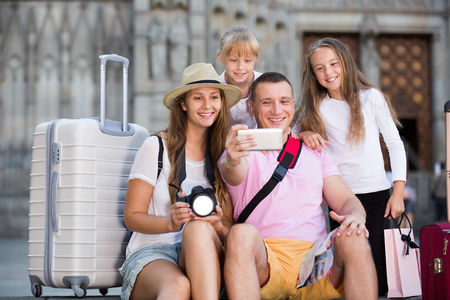 Active parents with two kids taking selfie near city sights 스톡 콘텐츠