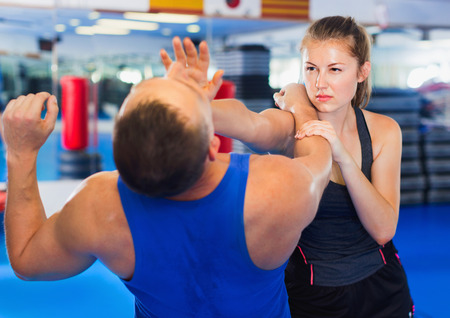 Strong bold  cheerful  woman is training with man on the self-defense course in gym.