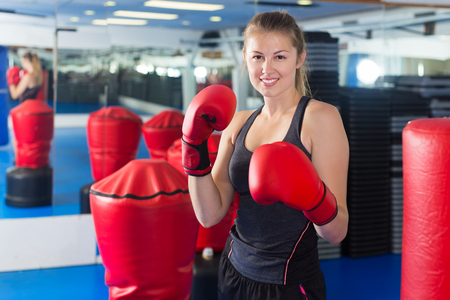 Portrait of young female who is boxing in gym