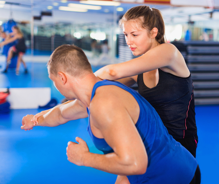 Positive cheerful  woman  is training captures with man on the self-defense course in gym.