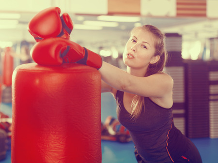 Portrait of active woman standing with punching bag in box gym