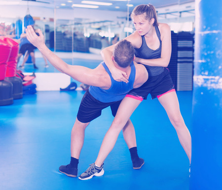 Adult female is fighting with trainer on the self-defense course for woman in sport club Archivio Fotografico
