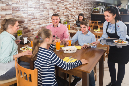 Young brunette waitress serving cheerful family in comfy family cafe Stock Photo