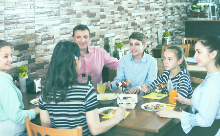 Big smiling family having fun and dinning in cafe Stock Photo