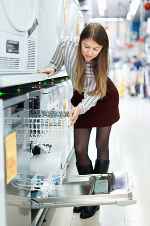 Modern happy  positive female housewife buying dishwasher in domestic appliances section