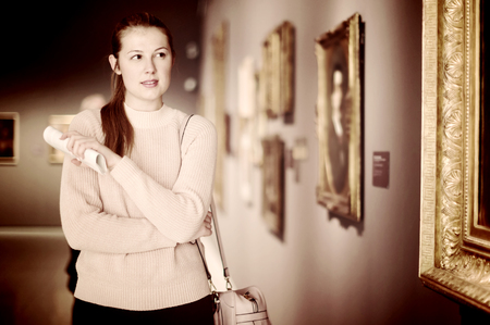 Portrait of young woman with guide looking at pictures in the museum of arts