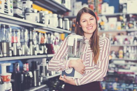 Modern female housewife buying liquidiser in household appliances shop
