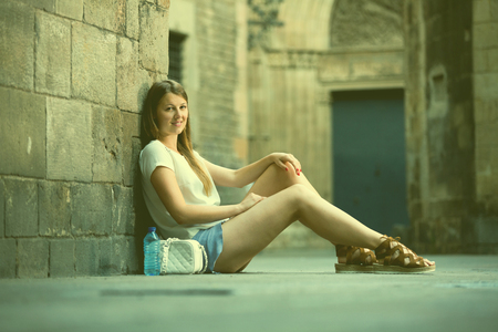 Romantic girl sitting near stone wall during walk on old town streets  Stock Photo