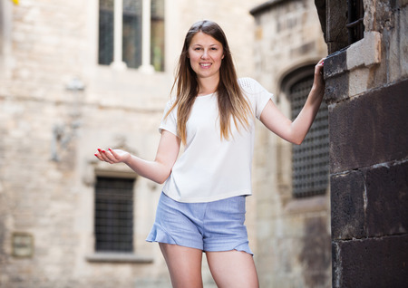 Happy young woman strolling around city standing near old stone wall  Stock Photo