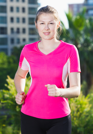 Adult woman in pink T-shirt is jogging around the urban.