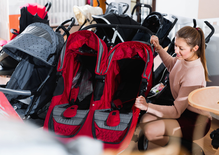 Happy cheerful  smiling female choosing carriage for twins in the children's store  Archivio Fotografico