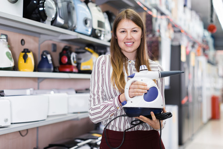 Polite salesgirl shows modern steam cleaner in store of kitchen appliances